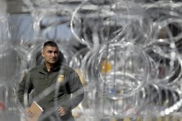 A U.S. Border Patrol agent looks through concertina wire during a tour of the San Ysidro port of entry Friday, Nov. 16, 2018, in San Diego. As thousands of migrants in a caravan of Central American asylum-seekers converge on the doorstep of the United States, what they won't find are armed American soldiers standing guard.  Instead they will see cranes installing towering panels of metal bars and troops wrapping concertina wire around barriers while military helicopters fly overhead, carrying border patrol agents.  (AP Photo/Gregory Bull)