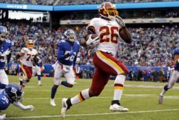 FILE -  In this Oct. 28, 2018, file photo, Washington Redskins running back Adrian Peterson (26) rushes for a touchdown against the New York Giants during an NFL football game in East Rutherford, N.J. Peterson ranks fifth in rushing with 587 yards, has four touchdowns, and is surrounded on the stats sheet by guys who weren't even in high school when Peterson broke in for Minnesota in 2007. (AP Photo/Adam Hunger, File)
