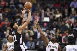 Washington Wizards forward Otto Porter Jr. (22) shoots against New Orleans Pelicans guard E'Twaun Moore (55) and guard Jrue Holiday, right, during the first half of an NBA basketball game Saturday, Nov. 24, 2018, in Washington. (AP Photo/Nick Wass)