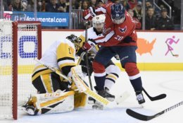 Washington Capitals center Lars Eller (20), of Denmark tires to get the pack past Pittsburgh Penguins goaltender Casey DeSmith (1) and defenseman Kris Letang, back, center, during the first period of an NHL hockey game, Wednesday, Nov. 7, 2018, in Washington. (AP Photo/Nick Wass)