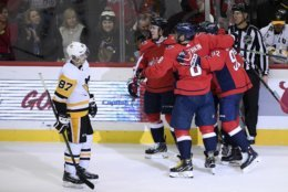 Pittsburgh Penguins center Sidney Crosby (87) skates by as members of the Washington Capitals including left wing Alex Ovechkin (8), of Russia, and center Evgeny Kuznetsov (92), of Russia, celebrate a goal by right wing T.J. Oshie, second from left, during the third period of an NHL hockey game, Wednesday, Nov. 7, 2018, in Washington. The Capitals won 2-1. (AP Photo/Nick Wass)