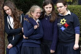 Students from the Yeshiva School in the Squirrel Hill neighborhood of Pittsburgh, react as the funeral procession for Dr. Jerry Rabinowitz passes their school en route to the Homewood Cemetery following a funeral service at the Jewish Community Center, Tuesday Oct. 30, 2018. Rabinowitz was one of those killed while worshipping at the Tree of Life synagogue on Saturday, Oct. 27, 2018. (AP Photo/Gene J. Puskar)