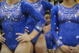 Simone Biles of the U.S. rests behind teammates during qualifying sessions for the Gymnastics World Chamionships at the Aspire Dome in Doha, Qatar, Saturday, Oct. 27, 2018. A bout with a kidney stone did little to slow Biles, as the reigning Olympic champion easily posted the top all-around score of 60.965 during the early portions of qualifying at the 2018 world championships on Saturday. (AP Photo/Vadim Ghirda)