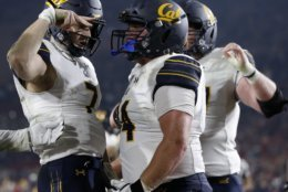 FILE - In this Saturday, Nov. 10, 2018, file photo, California quarterback Chase Garbers, left, celebrates with right guard Ryan Gibson after scoring a touchdown during the second half of an NCAA college football game against Southern California in Los Angeles. As big as beating USC was for Cal, a win over Stanford would be even more so. The Cardinal have won eight straight against the Golden Bears, many of them lopsided victories.  (AP Photo/Alex Gallardo, File)