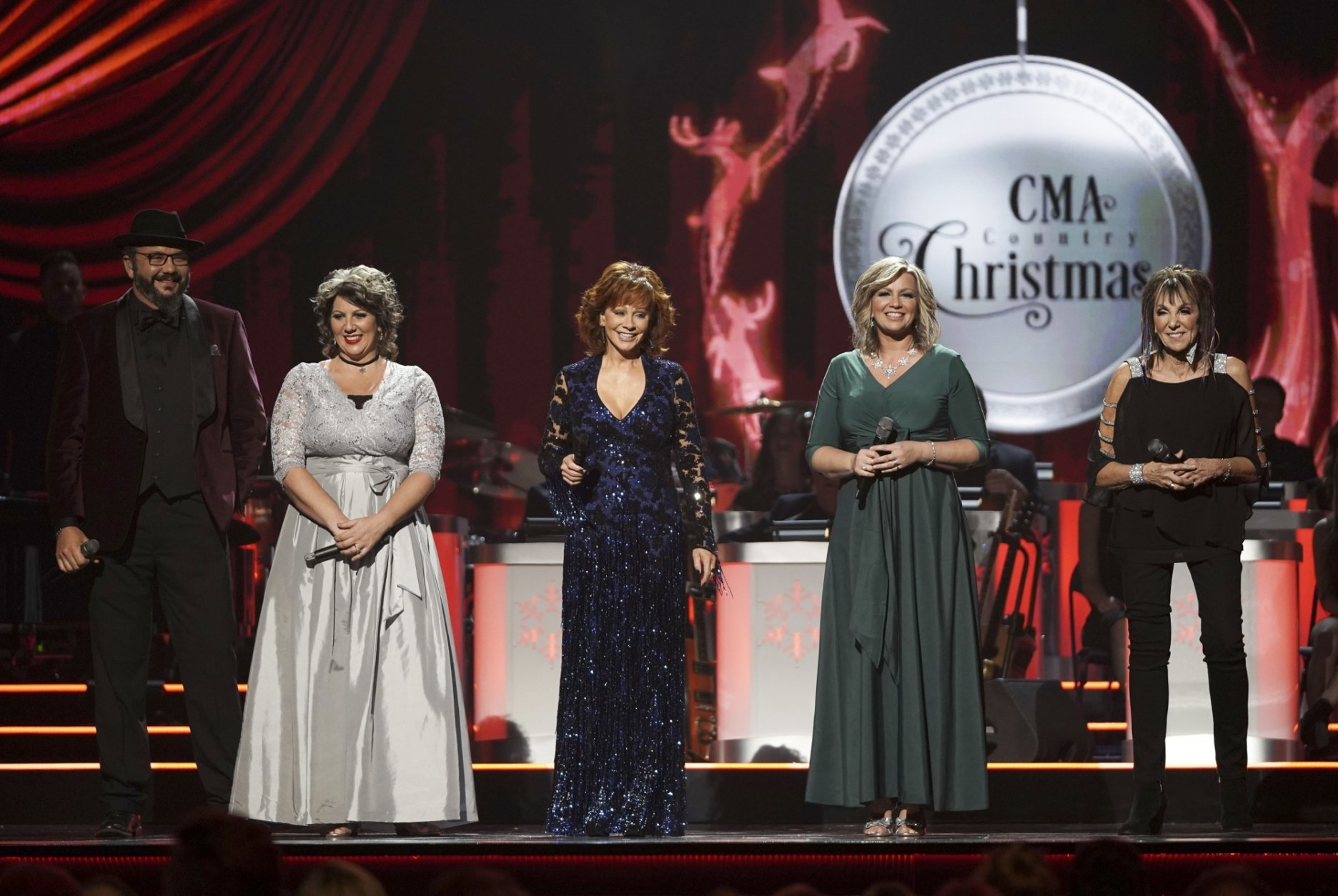"""This image released by ABC shows host Reba McEntire, center, with members of The Isaacs, from left, Ben Isaacs, Becky Isaacs Bowman, Sonya Isaacs Yeary and Lily Isaacs during the ninth annual """"CMA Country Christmas"""" airing Monday, Dec. 10,  at 8 p.m. EST on ABC. (Mark Levine/ABC via AP)"""