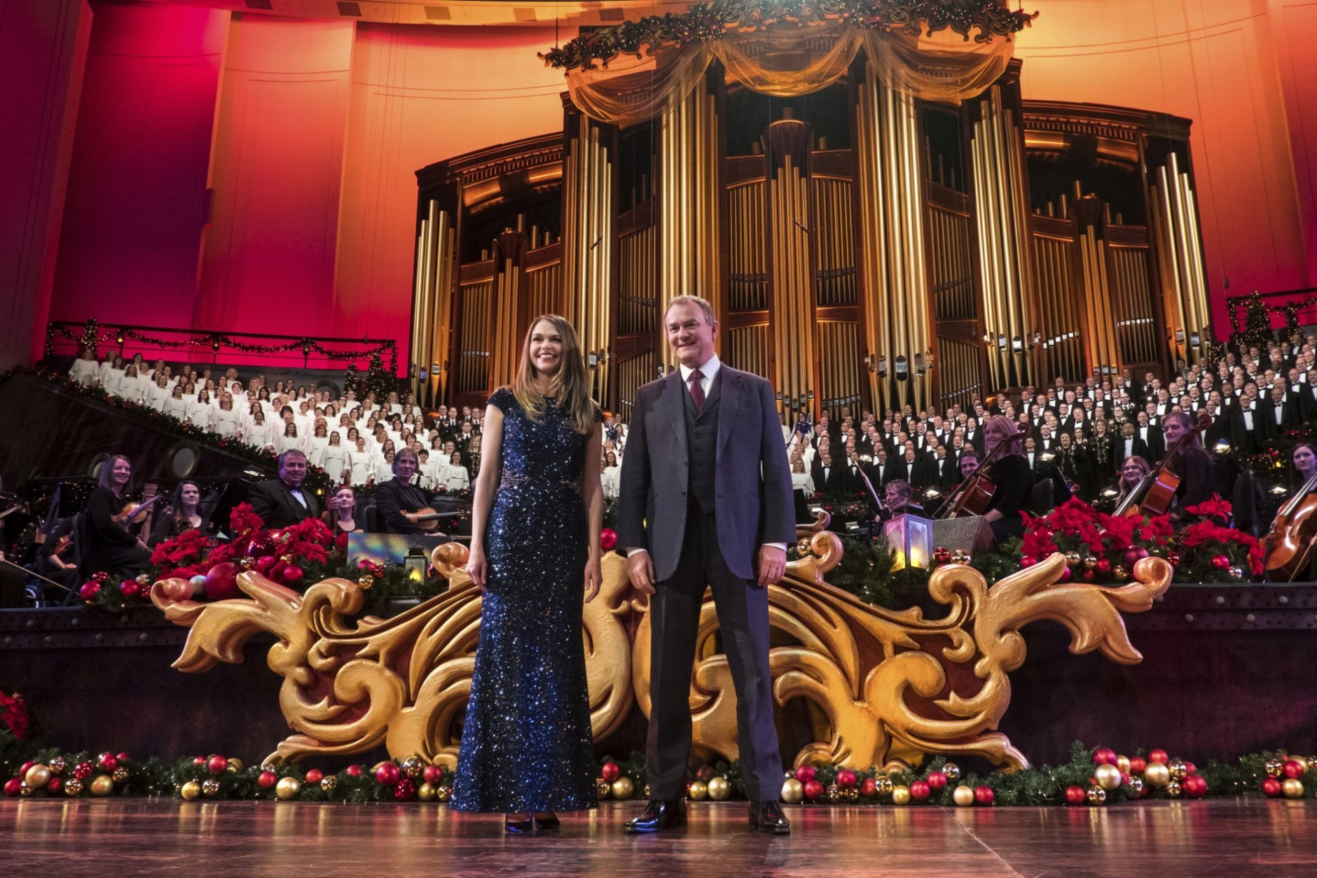 """This image released by PBS shows actors Sutton Foster, foreground left, and Hugh Bonneville, in """"Christmas with the Mormon Tabernacle Choir Featuring Sutton Foster and Hugh Bonneville,"""" airing Monday, Dec. 17 on PBS. (Justin Hackworth/PBS via AP)"""
