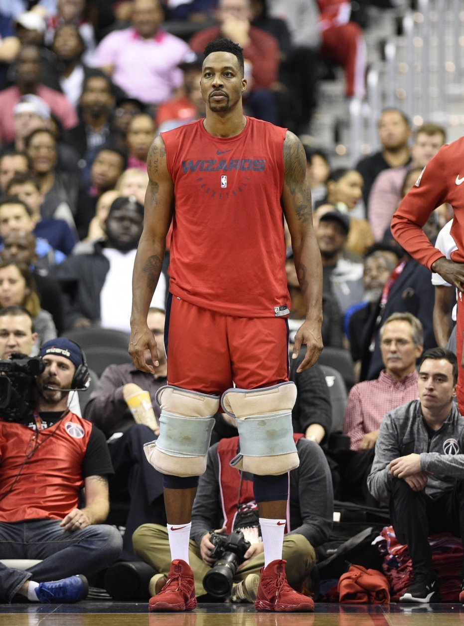 Washington Wizards center Dwight Howard watches from the sidelines with his knees wrapped during the second half of the team's NBA basketball game against the Oklahoma City Thunder, Friday, Nov. 2, 2018, in Washington. (AP Photo/Nick Wass)