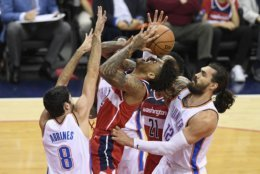 Oklahoma City Thunder center Steven Adams (12), of New Zealand, and guard Alex Abrines (8), of Spain, defend against Washington Wizards forward Kelly Oubre Jr., center, during the first half of an NBA basketball game Friday, Nov. 2, 2018, in Washington. (AP Photo/Nick Wass)