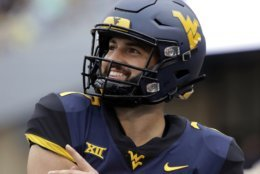 FILE - In this Sept. 8, 2018, file photo, West Virginia quarterback Will Grier (7) smiles during an NCAA college football game against Youngstown State, in Morgantown, W.Va. Grier, a senior, will play in his final home game Friday night, Nov. 23,  when No. 12 West Virginia hosts No. 6 Oklahoma.  (AP Photo/Raymond Thompson, File)