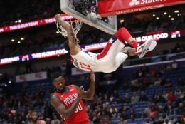 Washington Wizards center Dwight Howard (21) slam dunks over New Orleans Pelicans forward Julius Randle (30) in the first half of an NBA basketball game in New Orleans, Wednesday, Nov. 28, 2018. (AP Photo/Gerald Herbert)