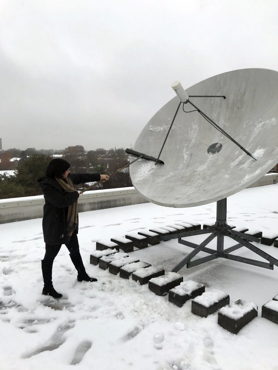 WTOP's Alicia Abelson braves the nasty weather to help clean the station's satellite dish. (WTOP/Chris Cichon)