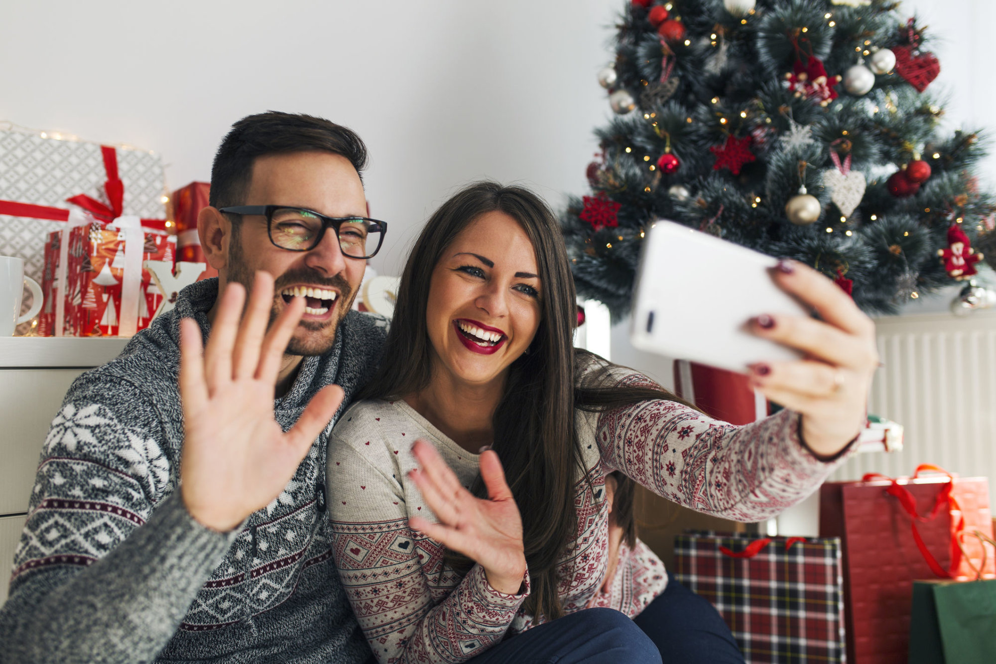 Smiling young couple waving and having video call