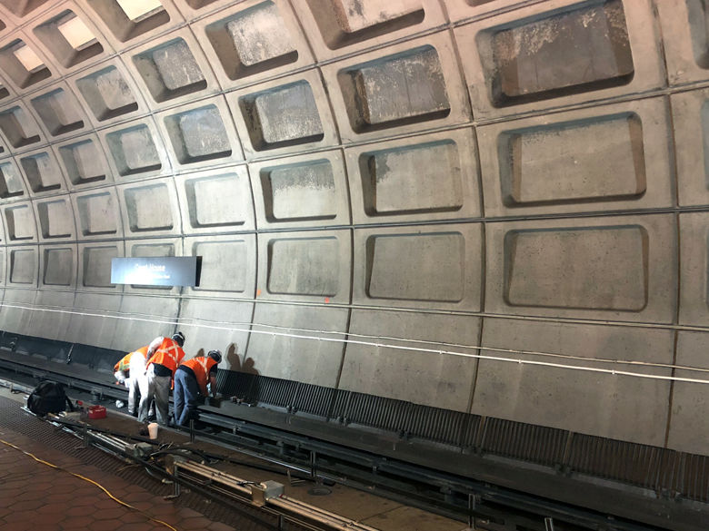 Workers installed track bed lighting in the Courthouse station in Arlington, Va. (WTOP/Megan Cloherty)