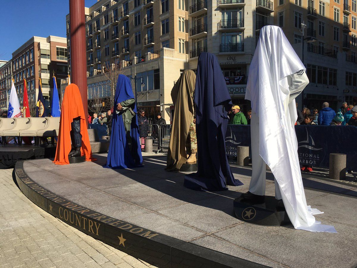 Sculptures representing the five branches of the U.S. Military before they are unveiled at National Harbor. (WTOP/Liz Anderson)