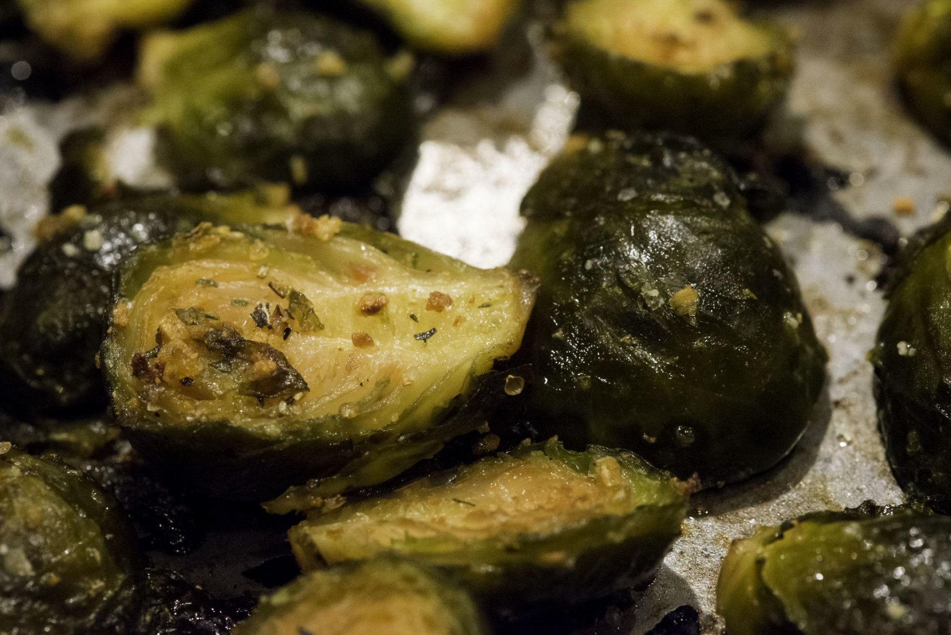 oven pan roasted brussel sprouts in olive oil, salt, sweet red peppers, spices and garlic shot in kitchen studio