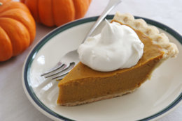 A slice of pumpkin (or sweet potato) pie with whipped cream and a fork.