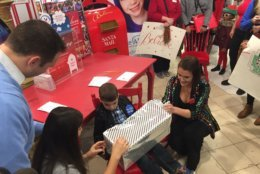 Nikolas got to spin his own wheel that led to Jenna Wallach, a manager at Macy's, to reach into her bag and pull out a big toy truck all wrapped up. (WTOP/John Domen)