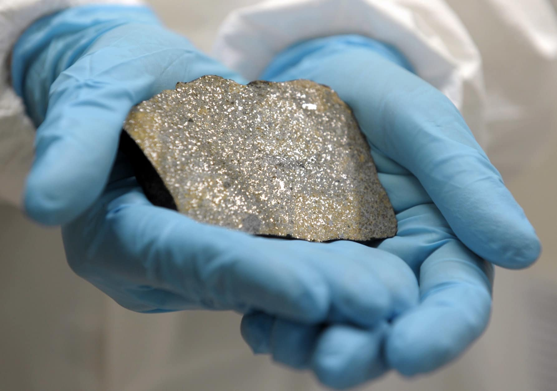 Catherine Corrigan a geologist with the Division of Meteorites at the Smithsonian Natural History Museum, holds a slice of a meteorite at a new meteorite lab in Suitland, Md., Monday, Nov. 28, 2011. (AP Photo/Susan Walsh)
