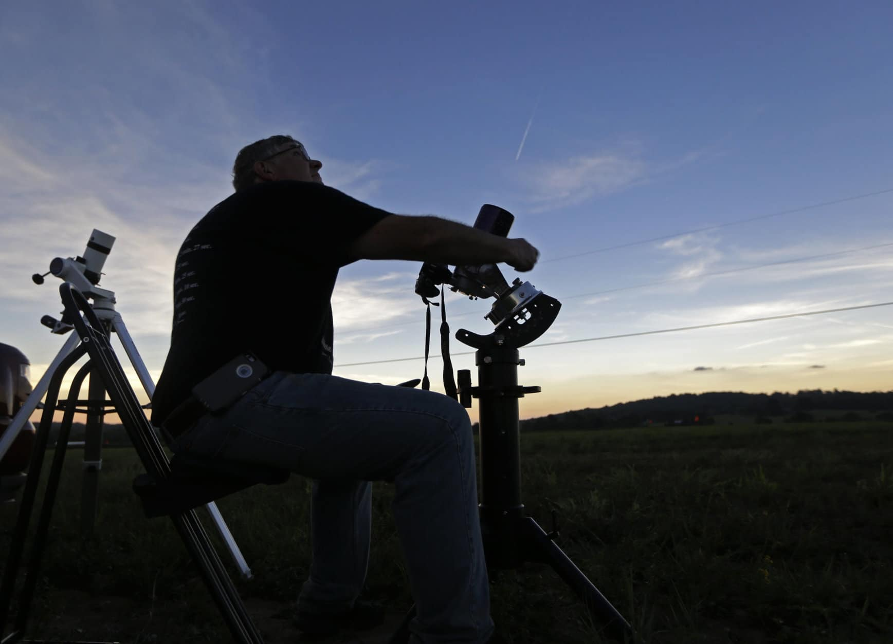 Mark Renz, of Rochester, N.Y, adjusts one of his telescopes during the period of total coverage during the solar eclipse Monday, Aug. 21, 2017, on the Orchard Dale historical farm near Hopkinsville, Ky. The location, which is in the path of totality, is also at the point of greatest intensity. (AP Photo/Mark Humphrey)
