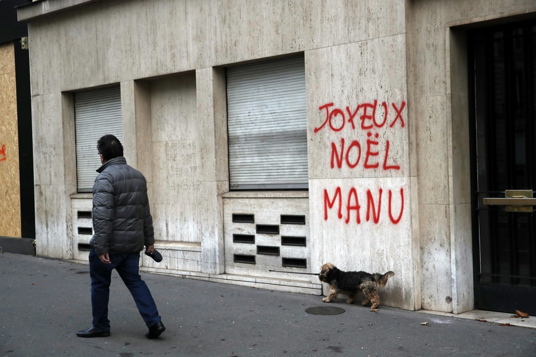 A man walks his dog past a tag reading : Happy Christmas Manu, referring to French President Emmanuel Macron, in Paris, Sunday, Dec. 9, 2018. Paris monuments reopened, cleanup workers cleared debris and shop owners tried to put the city on its feet again Sunday, after running battles between yellow-vested protesters and riot police left 71 injured and caused widespread damage to the French capital. (AP Photo/Christophe Ena)