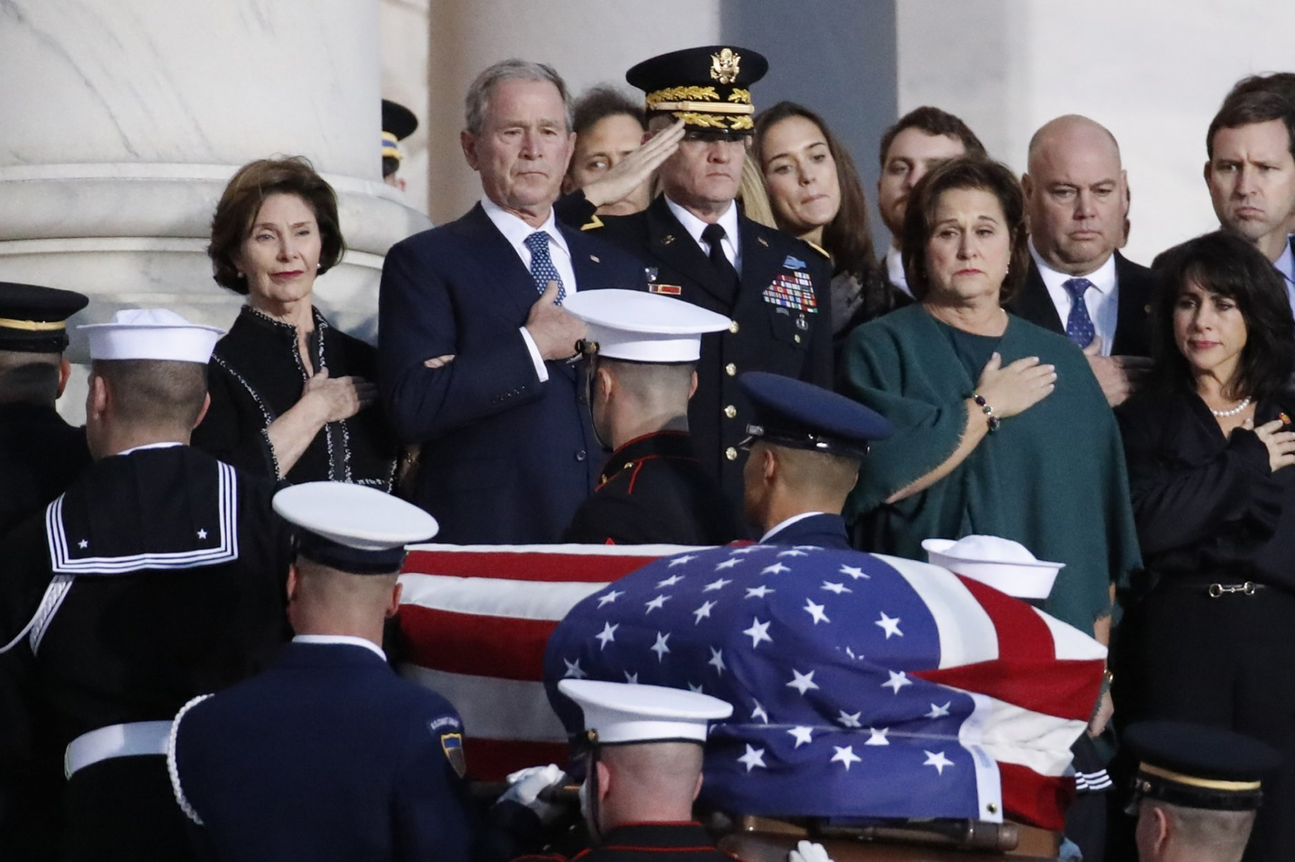 Former President George W. Bush, Laura Bush, left, and other family members watch as the flag-draped casket of former President George H.W. Bush is carried by a joint services military honor guard to lie in state in the rotunda of the U.S. Capitol, Monday, Dec. 3, 2018, in Washington. (AP Photo/Alex Brandon, Pool)