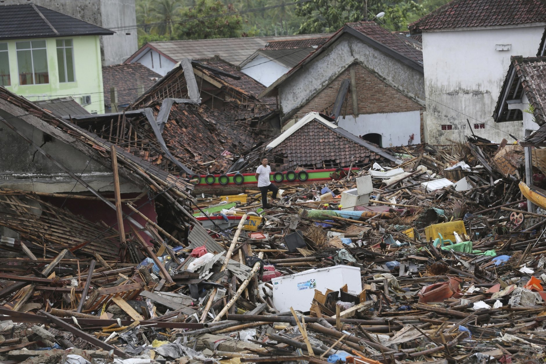 A man inspects the damage at a tsunami-ravaged village in Sumur, Indonesia, Tuesday, Dec. 25, 2018. The Christmas holiday was somber with prayers for tsunami victims in the Indonesian region hit by waves that struck without warning Saturday night.(AP Photo/Tatan Syuflana)