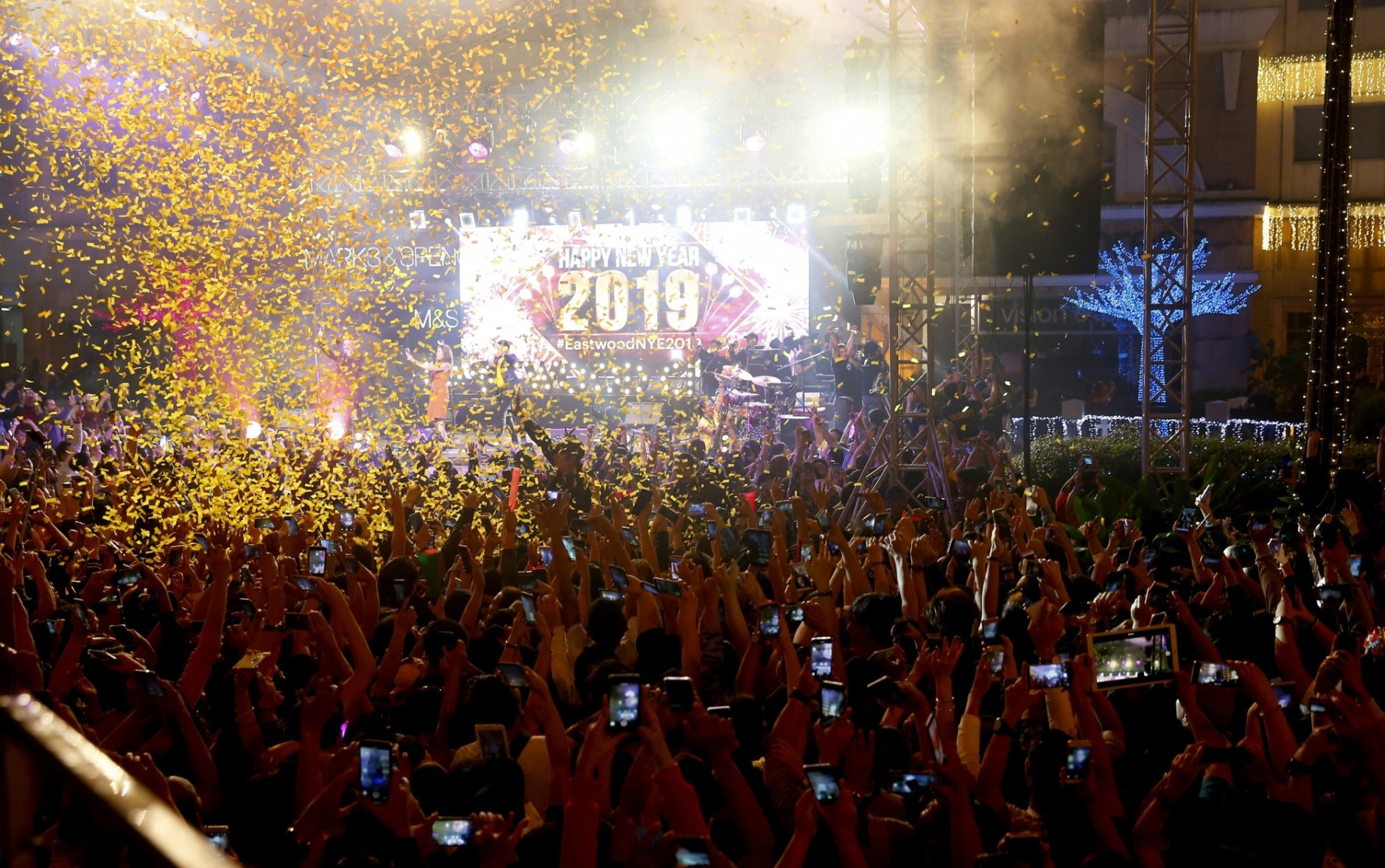Confetti rains down on revelers at the Eastwood Shopping Mall as Filipinos welcome the New Year Tuesday, Jan. 1, 2019, in suburban Quezon city northeast of Manila, Philippines. Filipinos welcome the New Year with the loudest noise possible including setting off powerful firecrackers in one of Asia's most violent celebrations. (AP Photo/Bullit Marquez)