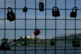 Alcatraz Island is shown behind a locks on a pier fence in San Francisco, Saturday, Dec. 22, 2018. A partial federal shutdown has been put in motion because of gridlock in Congress over funding for President Donald Trump's Mexican border wall. The company that provides ferry services to Alcatraz Island kept its daytime tours but canceled its behind-the-scenes and night tours for Saturday. (AP Photo/Jeff Chiu)