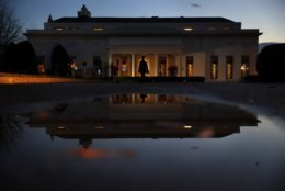 A person walks past the West Wing of the White House as it is reflected at dusk, Thursday, Dec. 20, 2018, in Washington, as the potential for a partial government shutdown looms. (AP Photo/Jacquelyn Martin)