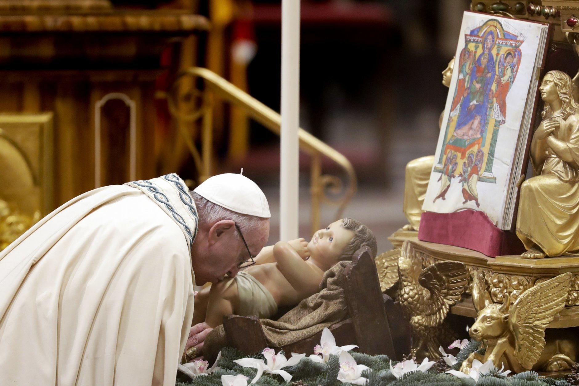 Pope Francis kisses a statue of Baby Jesus as he celebrates a new year's eve vespers Mass in St. Peter's Basilica at the Vatican, Monday, Dec. 31, 2018. (AP Photo/Andrew Medichini)