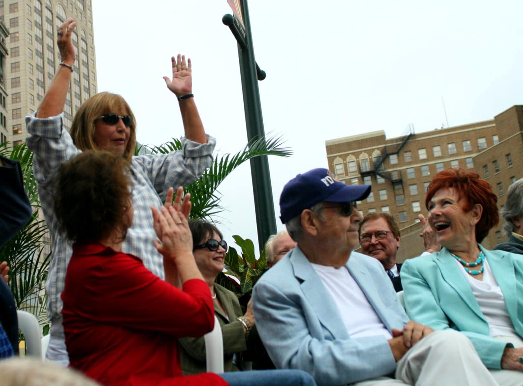 "Penny Marshall, standing left, acknowledges the crowd as Erin Moran, left, Cindy Williams, third left, Tom Bosley and Marion Ross, right, attend an unveiling of a bronze statue of the ""Happy Days"" character Arthur Fonzarelli, also known as ""The Fonz,"" Aug. 19, 2008, in Milwaukee, Wis. The program, which ran from 1974-1984, was based in Milwaukee. (AP Photo/Carrie Antlfinger)"