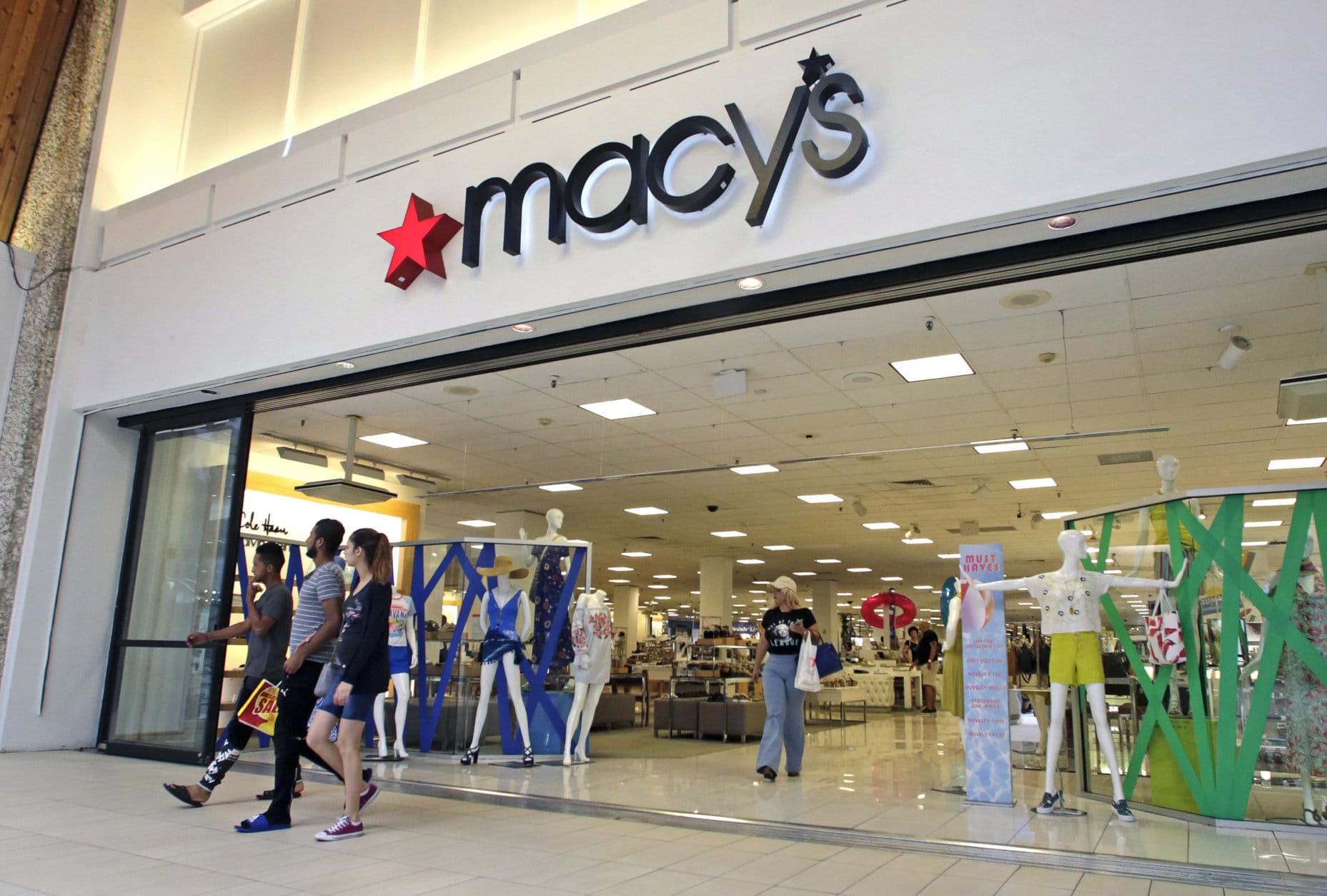 In this Wednesday, June 7, 2017, photo, people walk out of a Macy's department store in Hialeah, Fla. Macy's is increasing the number of temporary workers it's hiring for distribution and warehouses for the holiday season as it chases fast growing e-commerce sales. But overall holiday hiring will fall nearly 4 percent. (AP Photo/Alan Diaz)