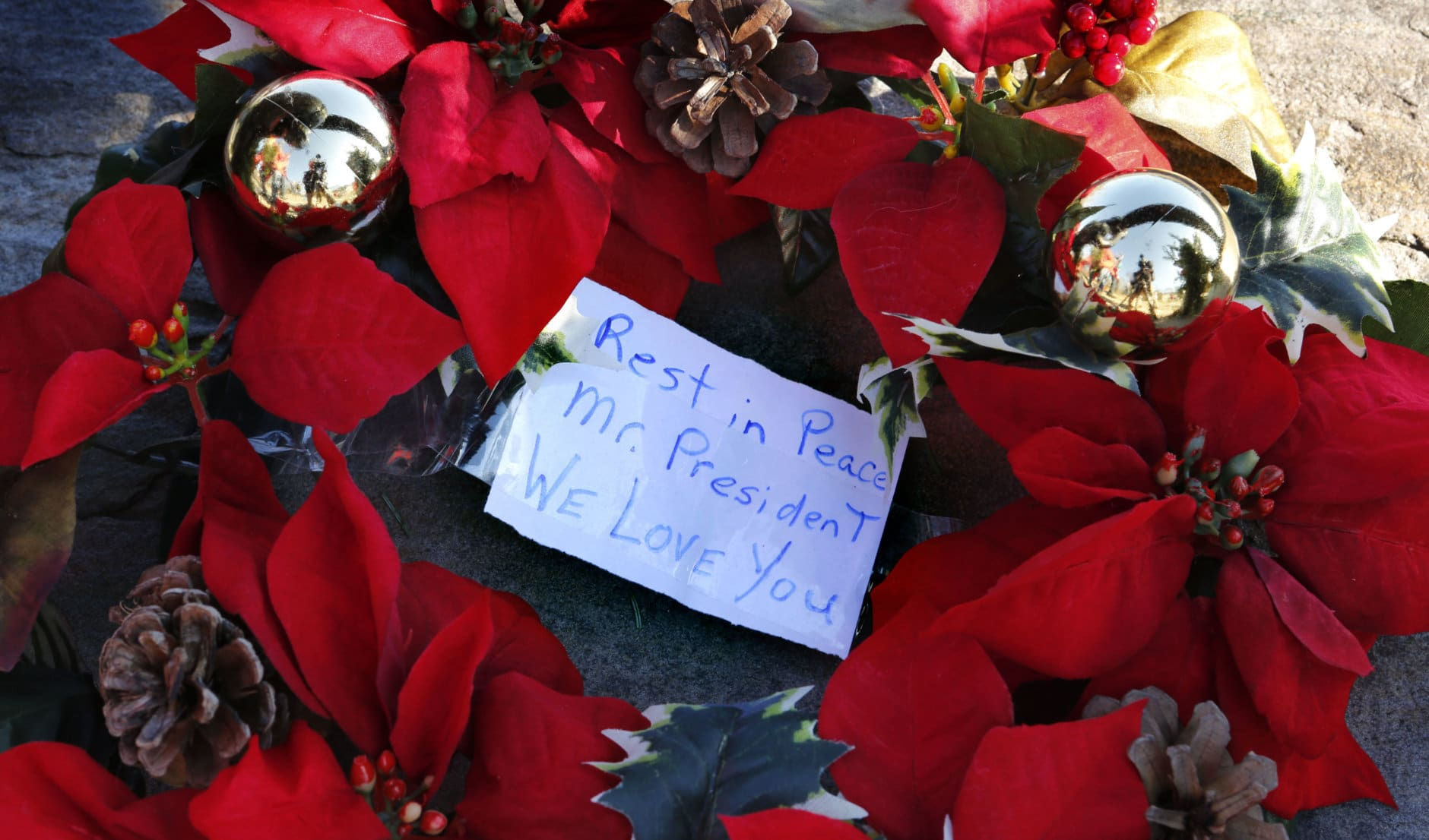 A wreath with a note to former President George H. W. Bush lay at a makeshift memorial across from Walker's Point, the Bush's summer home, Saturday, Dec. 1, 2018, in Kennebunkport, Maine. Bush died at the age of 94 on Friday, about eight months after the death of his wife, Barbara Bush. (AP Photo/Robert F. Bukaty)