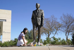 Thu Ton, of Dallas, places flowers at the base of a statue of former President George H.W. Bush outside the George H.W. Bush Presidential Library and Museum Saturday, Dec. 1, 2018, in College Station. Bush has died at age 94. Family spokesman Jim McGrath says Bush died shortly after 10 p.m. Friday, Nov. 30, 2018, about eight months after the death of his wife, Barbara Bush.(AP Photo/David J. Phillip)