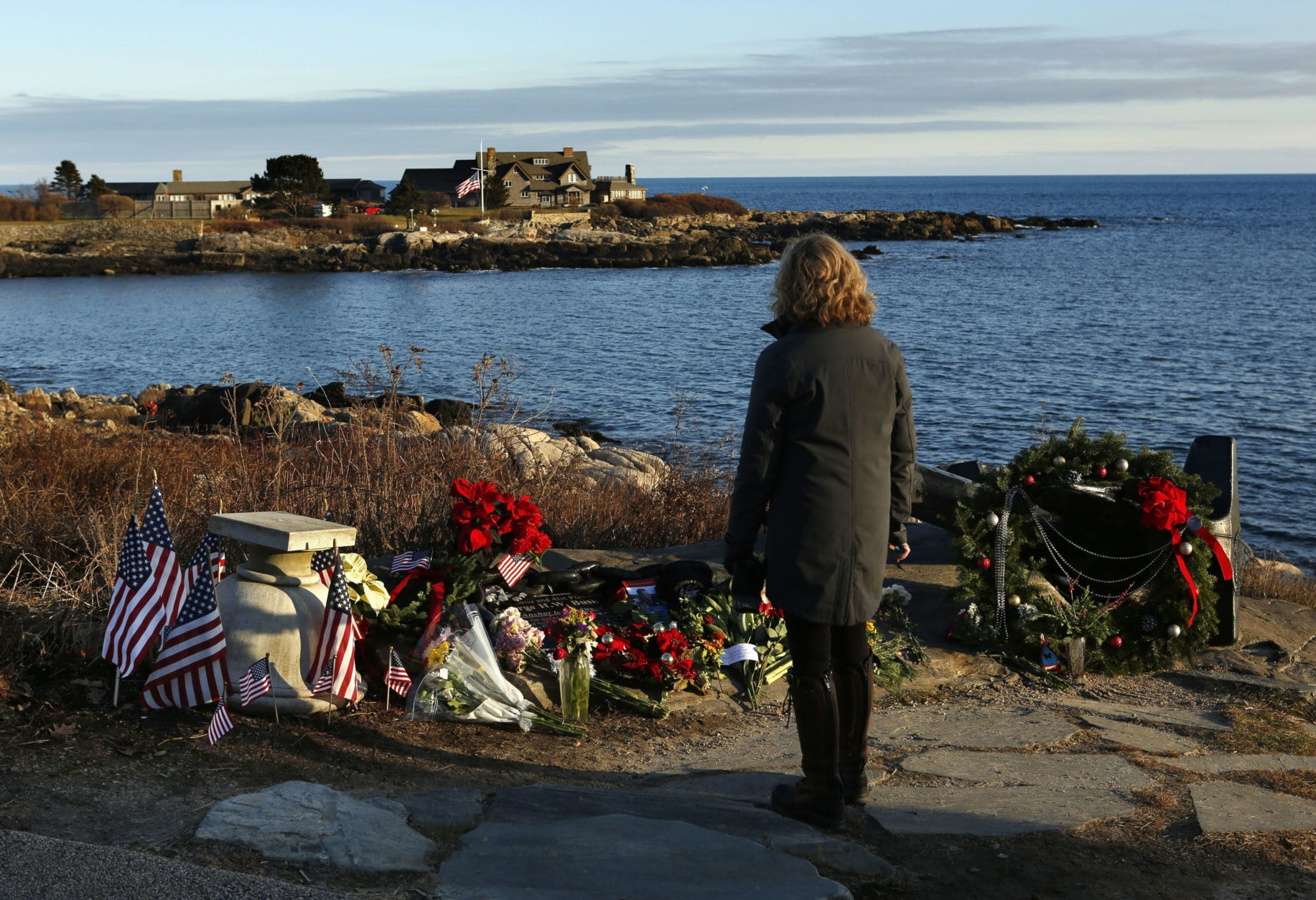 Cathy Rogers of Windham, Maine, pays her respects at a makeshift memorial for President George H. W. Bush across from Walker's Point, the Bush's summer home, Saturday, Dec. 1, 2018, in Kennebunkport, Maine. Bush died at the age of 94 on Friday, about eight months after the death of his wife, Barbara Bush. (AP Photo/Robert F. Bukaty)