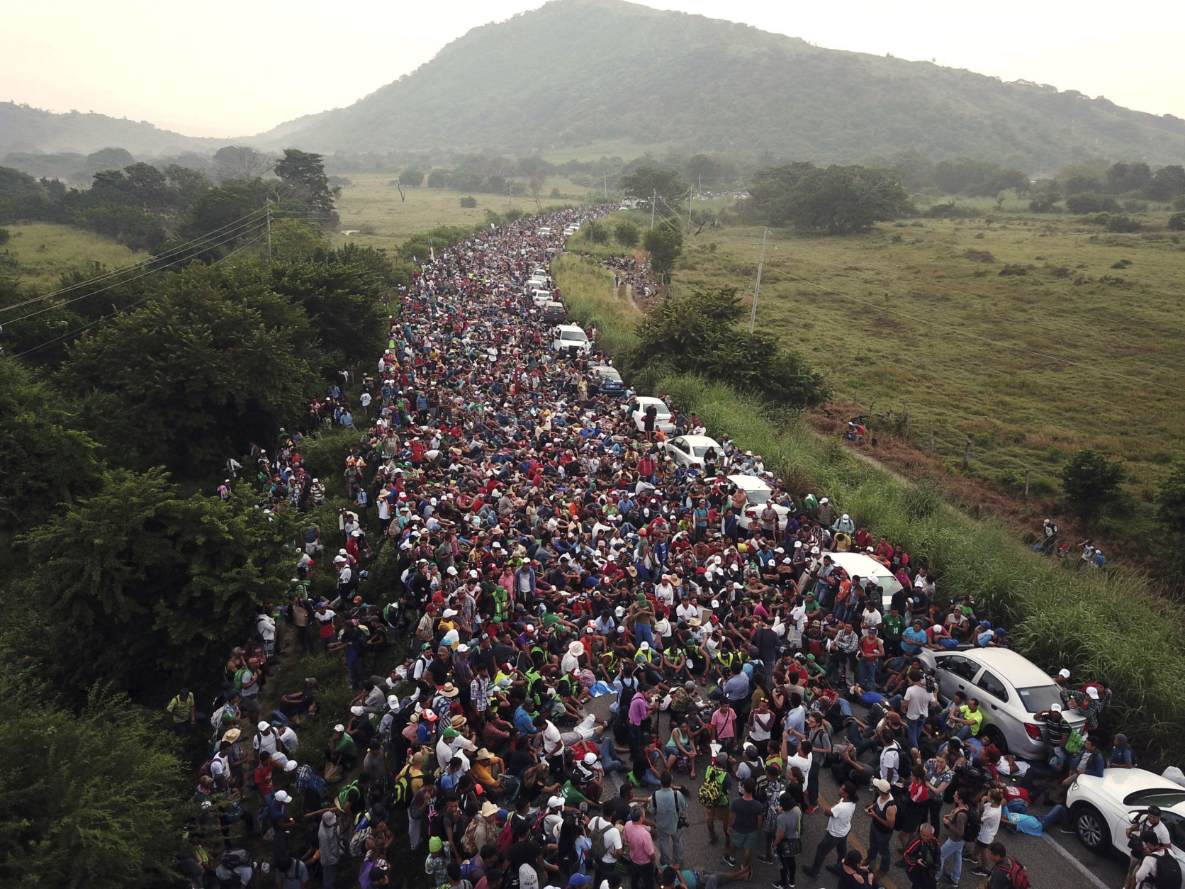 Members of a U.S.-bound migrant caravan stand on a road after federal police briefly blocked their way outside the town of Arriaga, Mexico, on Oct. 27, 2018. (AP Photo/Rodrigo Abd)