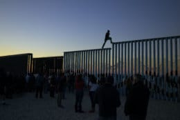 A man from Honduras walks along the top of the border structure separating Mexico and the United States on Nov. 14, 2018, in Tijuana, Mexico. (AP Photo/Gregory Bull)