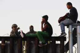 U.S. Border Patrol agents, left, speak with two Central American migrants as they sit atop the border structure separating Mexico and the United States in Tijuana, Mexico, on Nov. 14, 2018. (AP Photo/Gregory Bull)