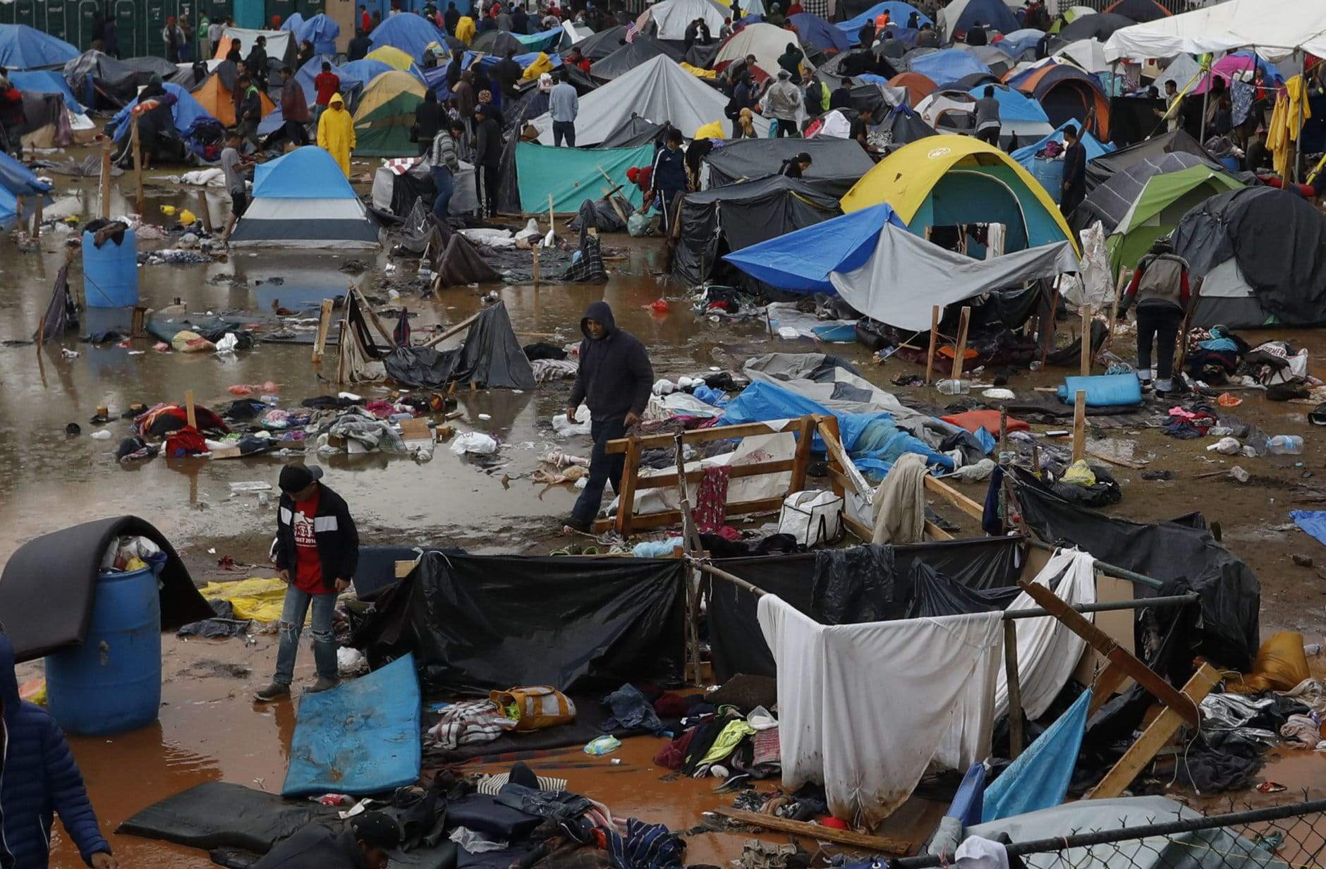Migrants walk amidst flooded tents after heavy rains poured down on a sports complex sheltering thousands of Central Americans in Tijuana, Mexico, on Nov. 29, 2018. Aid workers and humanitarian organizations expressed concerns about the unsanitary conditions at the severely overcrowded facility, where lice infestations and respiratory infections are rampant. (AP Photo/Rebecca Blackwell)