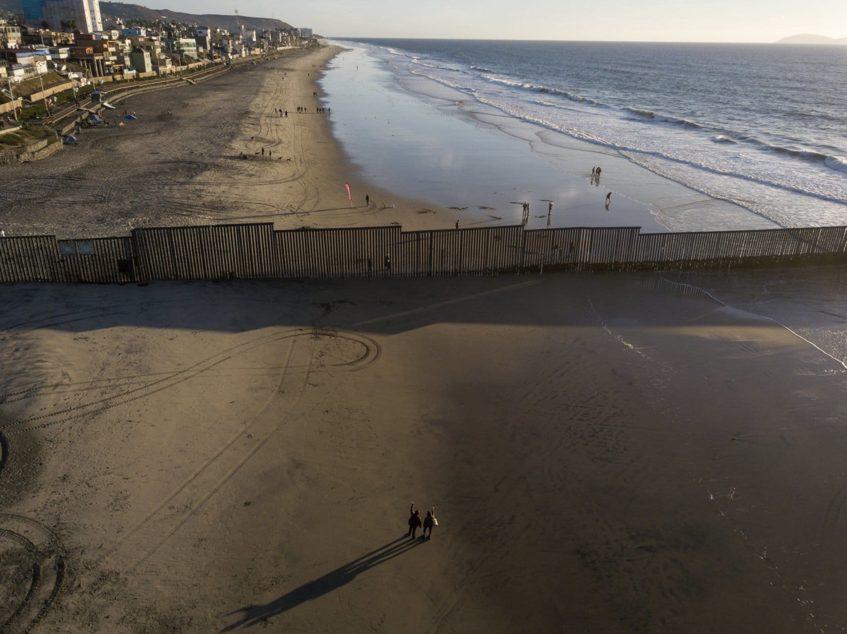 People on the U.S. side of the border wave at those on the Mexico side, at the border structure in San Diego on Nov. 23, 2018. (AP Photo/Rodrigo Abd)