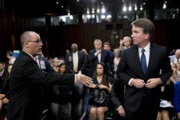 Fred Guttenberg, left, the father of Jamie Guttenberg, who was killed in the high school shooting in Parkland, Fla., attempts to shake hands with Brett Kavanaugh, President Donald Trump's Supreme Court nominee, as he leaves for a lunch break during his appearance before the Senate Judiciary Committee on Capitol Hill in Washington on Sept. 4, 2018. Kavanaugh did not shake his hand. (AP Photo/Andrew Harnik)