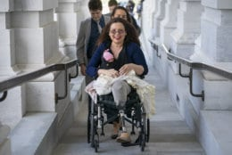 Sen. Tammy Duckworth, D-Ill., arrives at the Capitol for a close vote with her new daughter, Maile, bundled against the wind, in Washington on April 19, 2018. In an historic change in Senate rules, the lawmakers decided to allow babies of members on the floor during votes. (AP Photo/J. Scott Applewhite)
