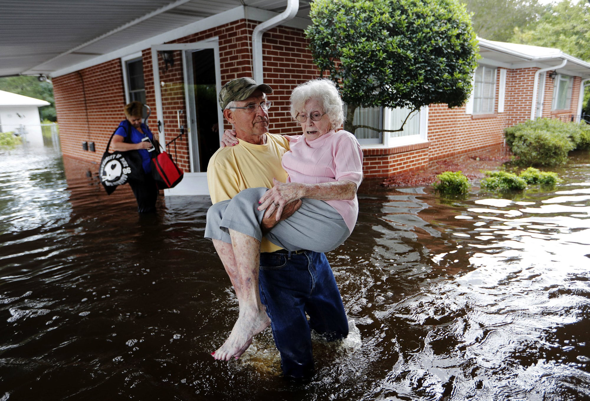 Bob Richling carries Iris Darden, 84, out of her flooded home as her daughter-in-law, Pam Darden, gathers her belongings in the aftermath of Hurricane Florence in Spring Lake, N.C. on Sept. 17, 2018. (AP Photo/David Goldman)