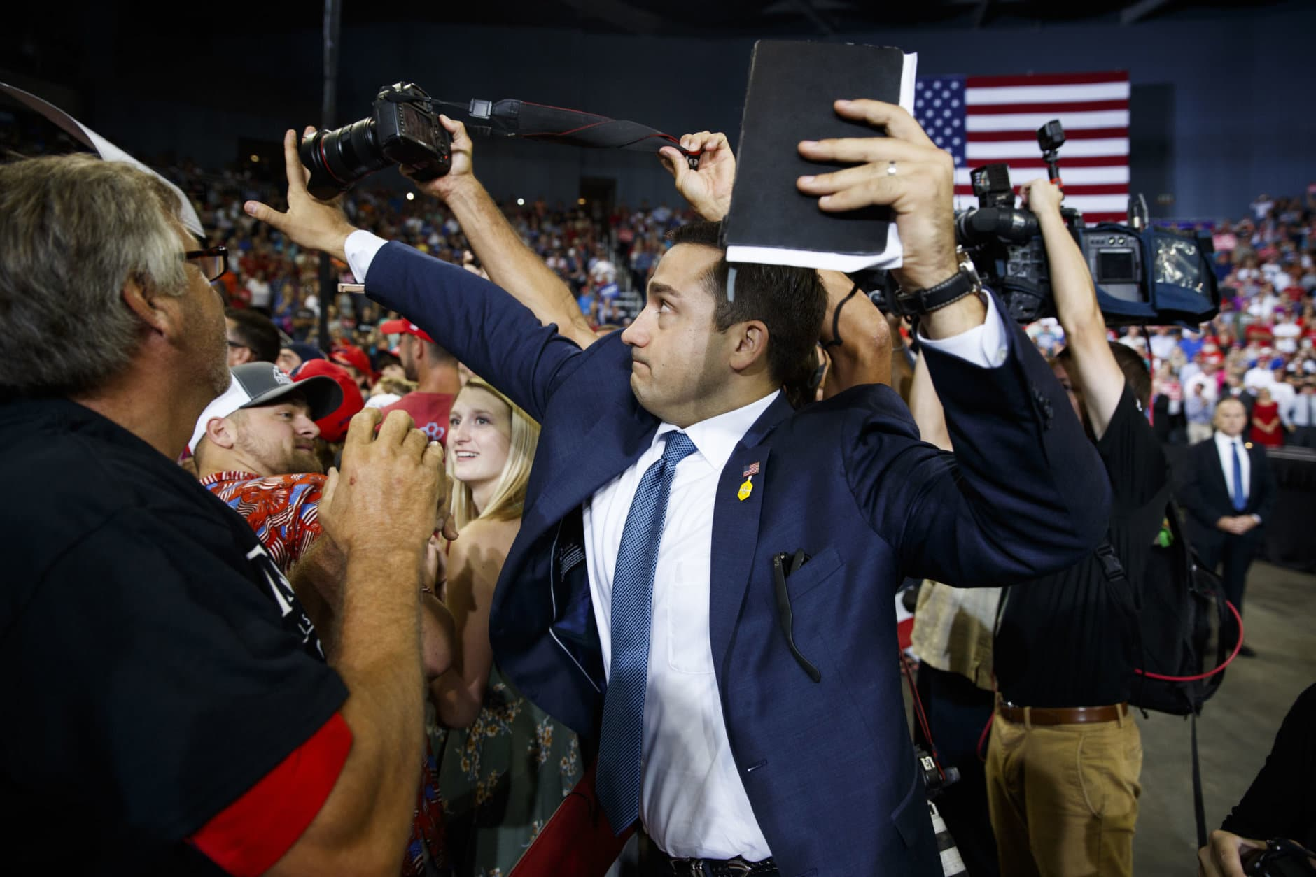 A volunteer member of the advance team for President Donald Trump blocks a camera as a photojournalist attempts to take a photo of a protester during a campaign rally in Evansville, Ind., on Aug. 30, 2018. (AP Photo/Evan Vucci)