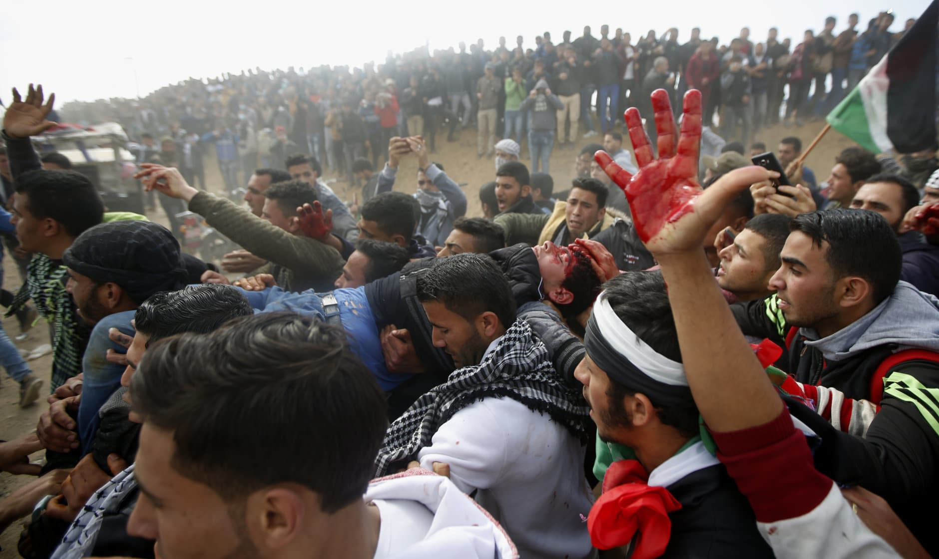 Palestinian protesters evacuate a wounded youth during clashes with Israeli troops along the Gaza Strip border with Israel, east of Khan Younis, Gaza Strip, on March 30, 2018. (AP Photo/Adel Hana)