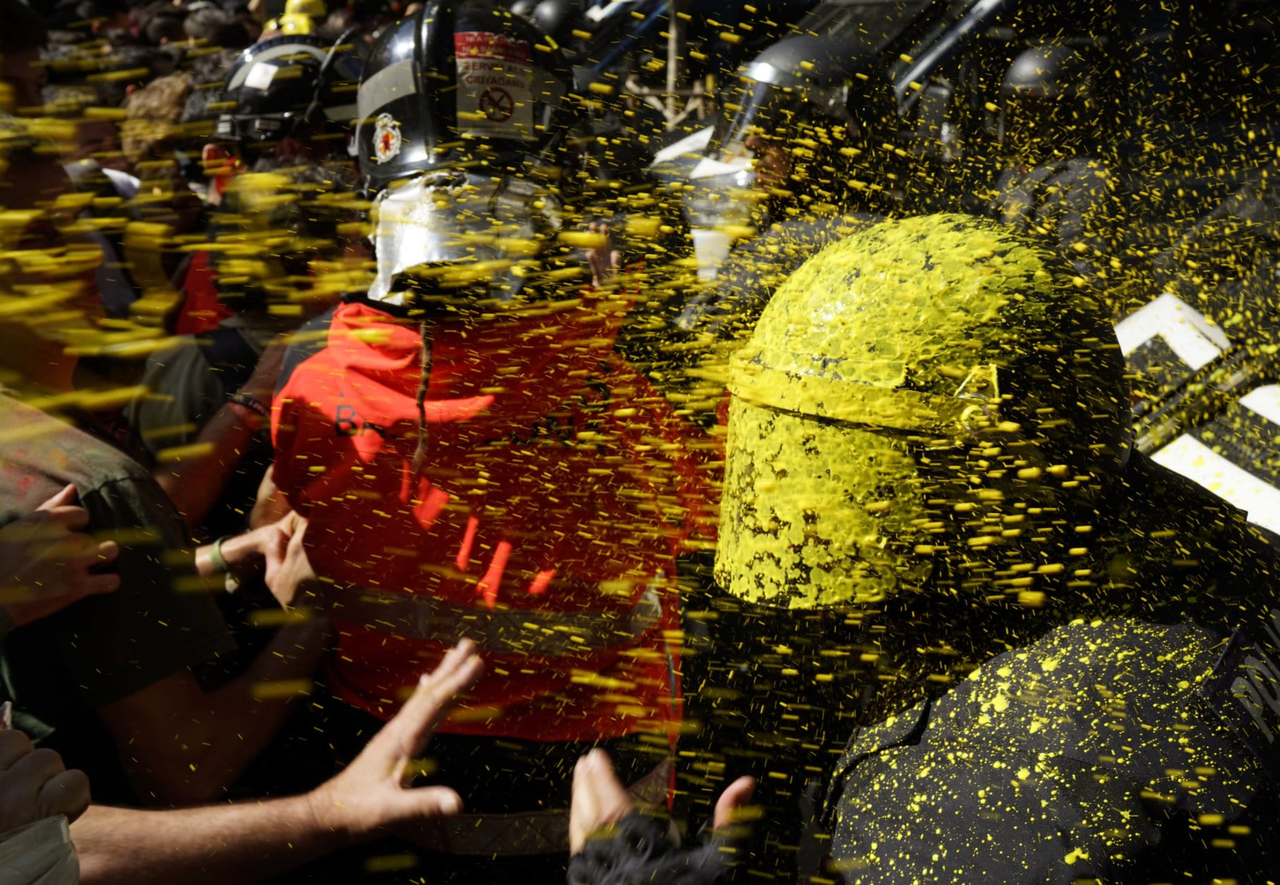Pro independence demonstrators throw paint at Catalan police officers during clashes in Barcelona, Spain, on Sept. 29, 2018, as tensions increase before the anniversary of the Spanish region's illegal referendum on secession that ended in violent raids by security forces. (AP Photo/Daniel Cole)