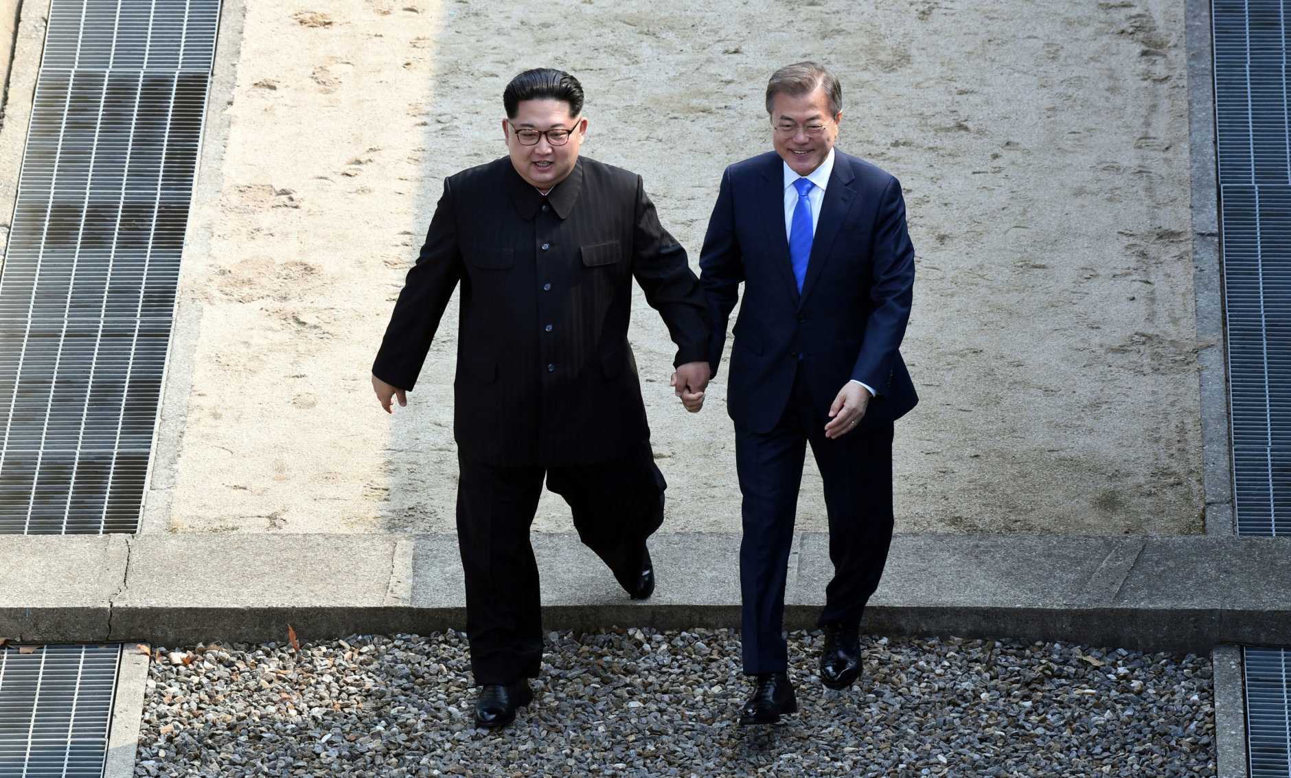 North Korean leader Kim Jong Un, left, and South Korean President Moon Jae-in cross the military demarcation line at the border village of Panmunjom in Demilitarized Zone on April 27, 2018. (Korea Summit Press Pool via AP)