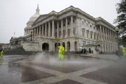 A worker power washes the plaza on the East Front of the U.S. Capitol,  Sunday, Dec. 2, 2018, in Washington in preparation of President George H.W. Bush lying in state. Bush, who died late Friday at his Houston home at age 94, is to be honored with a state funeral at National Cathedral in the nation's capital on Wednesday, followed by burial Thursday on the grounds of his presidential library at Texas A&M.  Before that, his body will lie in state in the Capitol Rotunda for a public viewing from his arrival in Washington on Monday until Wednesday morning.  (AP Photo/Alex Brandon)