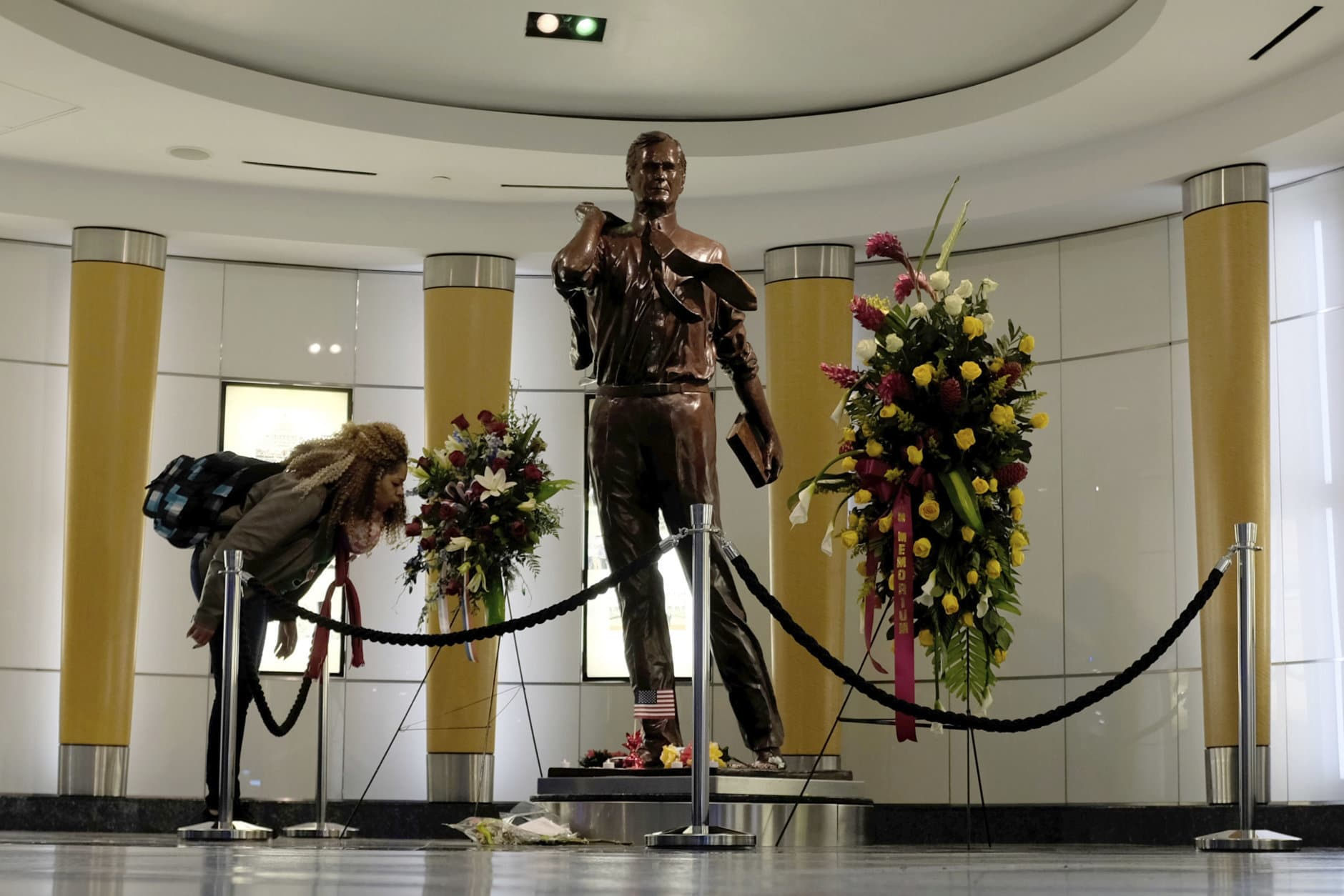 An air traveler visits a statue of former President George H.W. Bush as she arrives at George Bush Intercontinental Airport, Sunday, Dec. 2, 2018, in Houston. Bush, who died late Friday at his Houston home at age 94, is to be honored with a state funeral at National Cathedral in the nation's capital on Wednesday, followed by burial Thursday on the grounds of his presidential library at Texas A&M University. (AP Photo/Kiichiro Sato)