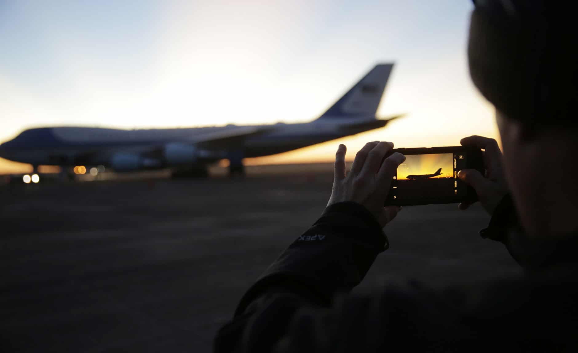 A member of the military takes a photo as the sun rises behind Special Air Mission 41, the plane that will transfer the casket of former President George H.W. Bush to Washington, Monday, Dec. 3, 2018, in Houston. Bush, died late Friday at his Houston home at age 94, is to be honored with a state funeral at National Cathedral in the nation's capital on Wednesday, followed by burial Thursday on the grounds of his presidential library at Texas A&M. (AP Photo/Eric Gay)